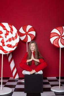 小さな女の子は、赤い背景の上の巨大なクリスマスキャンディーでリラックスします。