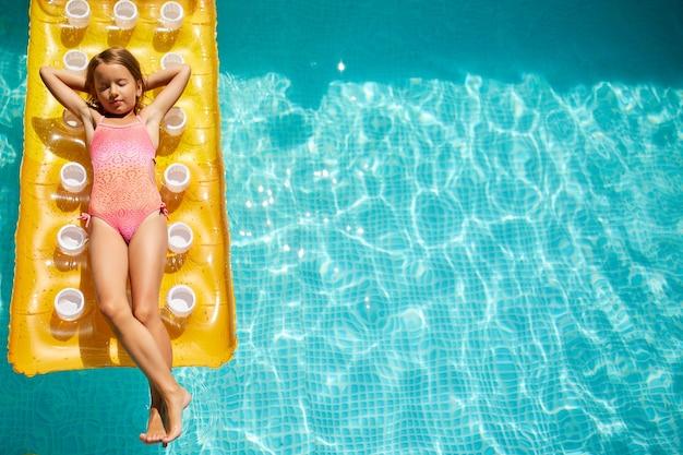 어린 소녀는 수영장에서 휴식을 취하고, 선탠을 즐기고, 풍선 노란색 매트리스에서 수영하고, 가족 휴가, 열대 휴양지, 위에서보기, 공간 복사에 물에서 재미를 가지고 있습니다.