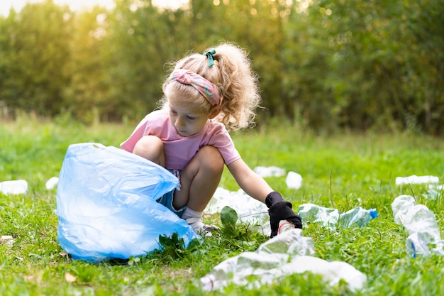 A little girl removes plastic garbage and puts it in a biodegradable garbage bag outdoors. the concept of ecology, waste processing and nature protection. environmental protection.