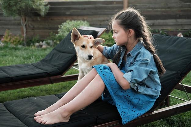 Маленькая девочка отдыхает на шезлонге со своей собакой на открытом воздухе в стране