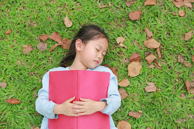 Little girl resting with book lying on green grass with dried leaves in the summer garden.