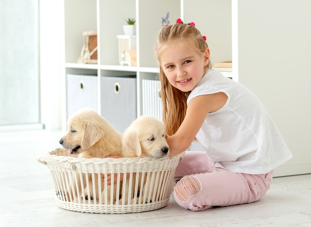 Little girl and retriever puppies