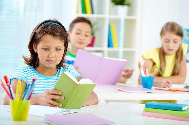 Маленькая девочка рассматривает свою книгу