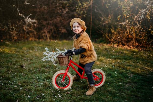 바구니에 꽃과 함께 이른 봄에 자전거를 타는 어린 소녀