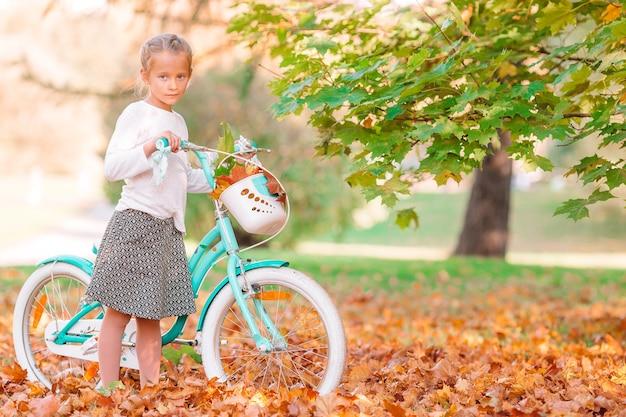 公園の屋外の美しい秋の日に自転車に乗る少女