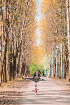 야외 공원에서 아름다운 가을 날에 자전거를 타는 어린 소녀