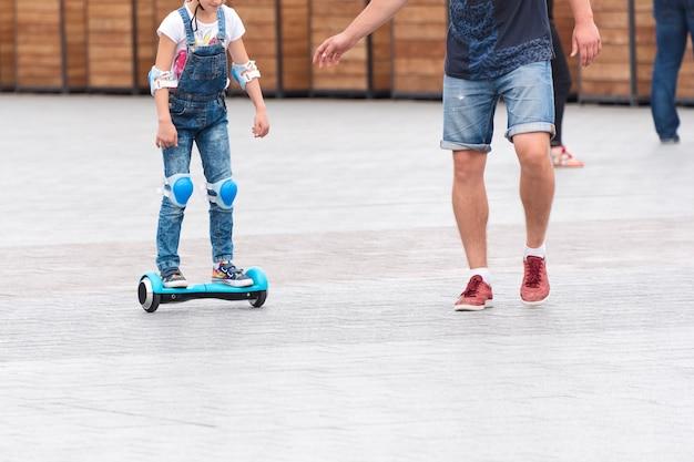 Маленькая девочка катается на ховерборде на городской площади