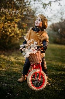 이른 봄에 공원에서 빨간 자전거를 타는 어린 소녀