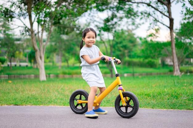 Little girl riding balance bike in the park