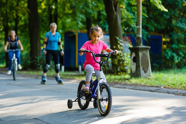 Little girl riding bicycle in city park.