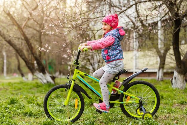 Little girl riding bike in the field.