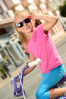 Little girl riding a bike on the street in city.