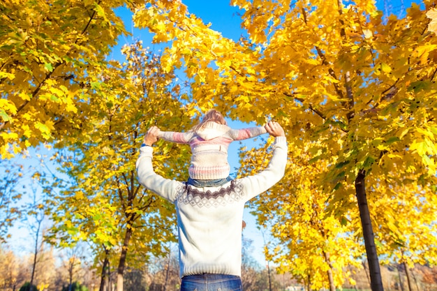Little girl riding on father's shoulders in autumn park