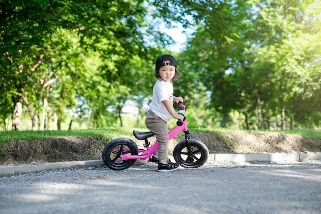 Маленькая девочка катается на розовом велотренажере в парке