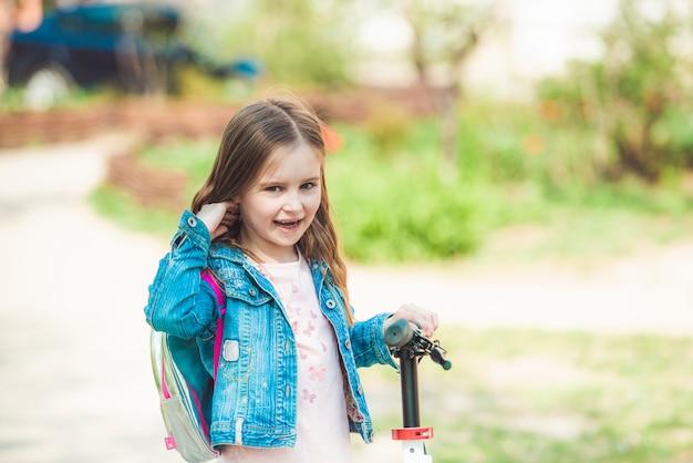 Маленькая девочка верхом на скутере