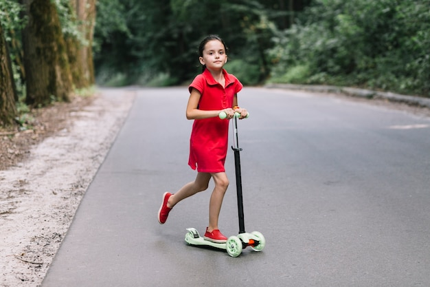 Little girl riding push scooter on road