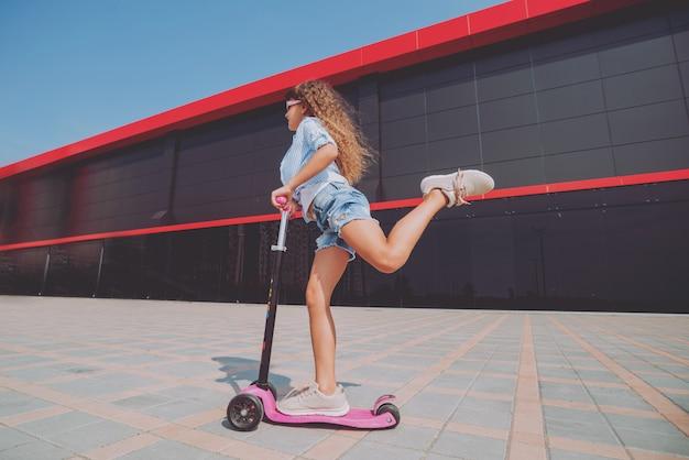 Маленькая девочка верхом скутер на открытом воздухе.
