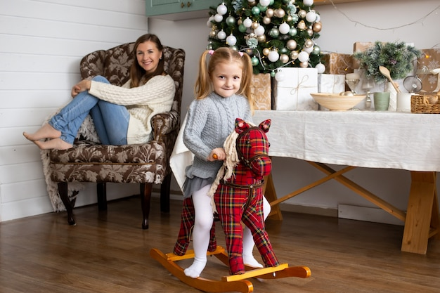 Little girl riding toy horse and her mother in christmas kitchen at home.