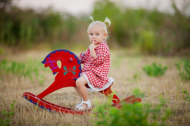 Little girl riding a toy horse for a walk in the summer