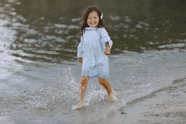 Bambina sul fiume. la ragazza spruzza l'acqua. ragazza in un vestito blu.