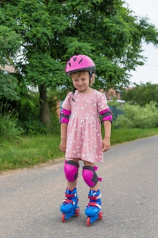 A little girl roller skates in full protection on a village road