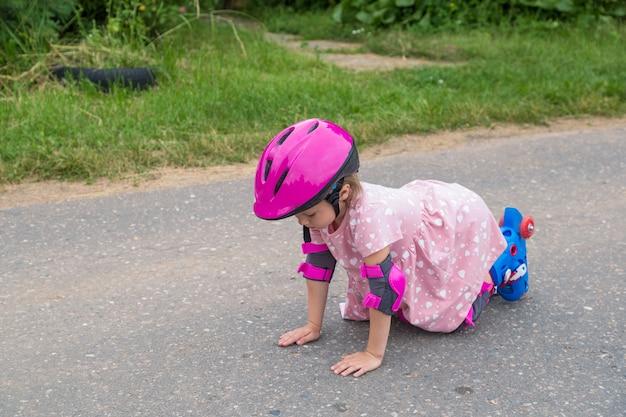 A little girl roller skating in full protection fell on the asphalt
