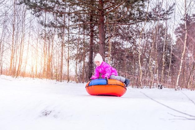 Маленькая девочка катится по горному склону на надувных санках-сырниках. концепция - люди и зимние виды спорта.