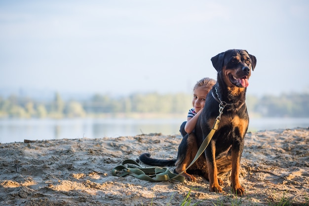 Little girl and rottweiler dog cuddling on the edge of a cliff enjoying a warm morning in the forest