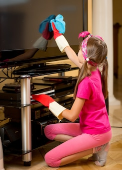 Little girl in rubber gloves cleaning tv screen from dust with blue cloth