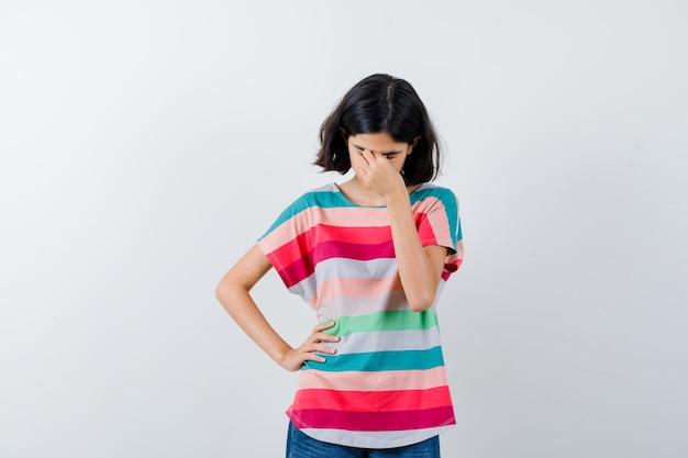 Маленькая девочка протирает глаза и нос в футболке и выглядит усталой, вид спереди.
