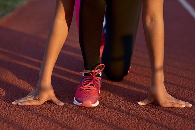 Маленькая девочка-бегун стоит в стартовой позиции перед спринтом