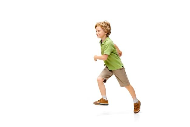 Маленькая девочка бежит и прыгает счастливой на белом