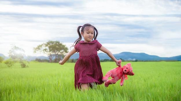 여름에 녹색 초원에서 재미를 실행하는 어린 소녀; 즐기는 자연