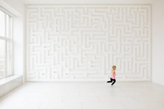 Маленькая девочка бежит возле стены лабиринта в белой комнате