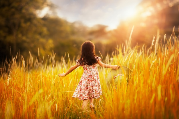 Little girl running in outdoor park with sunny sky