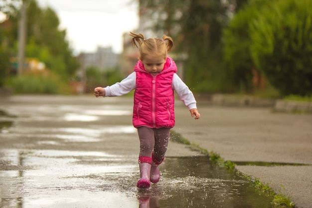 The little girl running through a puddle