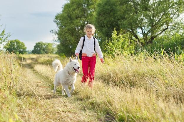 牧草地で犬と一緒に走っている少女。自然の中でペットと遊ぶ子供、子供の健康的なアクティブなライフスタイル、動物と人間の友情
