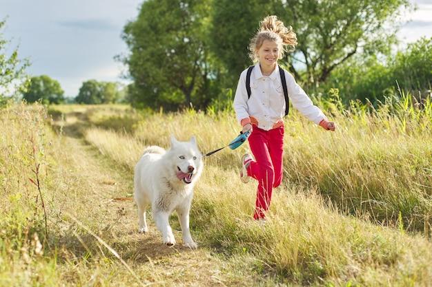 牧草地で犬と一緒に走っている少女