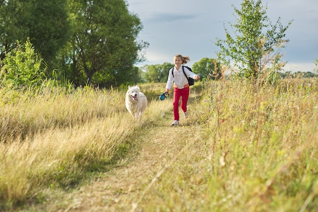 Little girl running with dog in meadow.