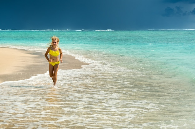 A little girl runs along the beach of the tropical island of mauritius in the indian ocean.