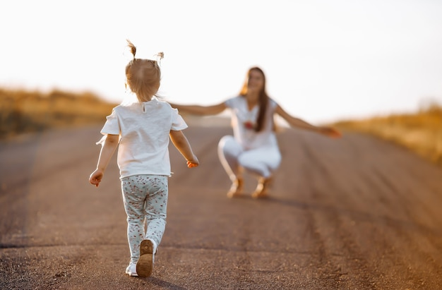 少女は日没の夏にママに会うために道路に沿って走ります
