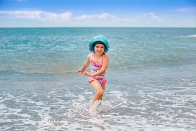 Little girl runs on the beach on the waves of the sea with splashes.