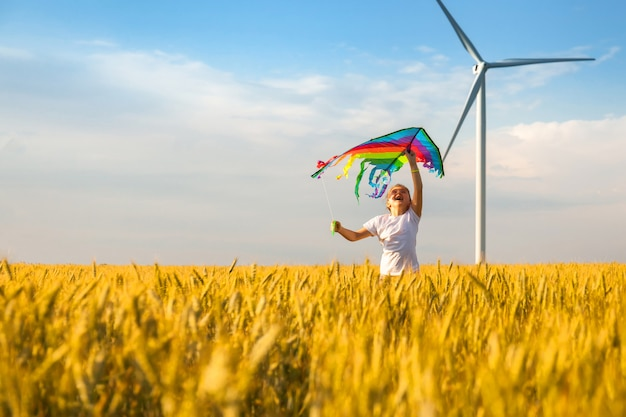 Little girl runs in a wheat field with a kite