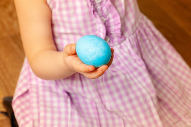 Little girl's hand holding painted easter egg. close up shot