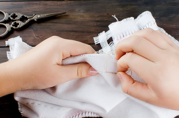 Little girl's hands embroiding cross on the canvas.