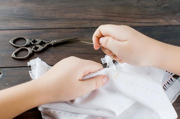 キャンバスに小さな女の子の手がクロスを刺繍します。