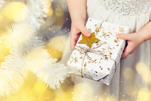 Little girl's hands holding white gift box, new year present, christmas lights