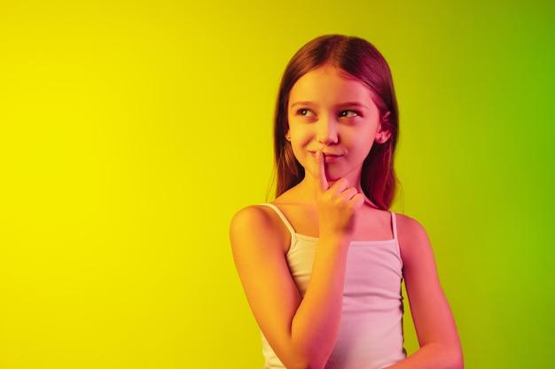 Little girl's portrait isolated on neon wall
