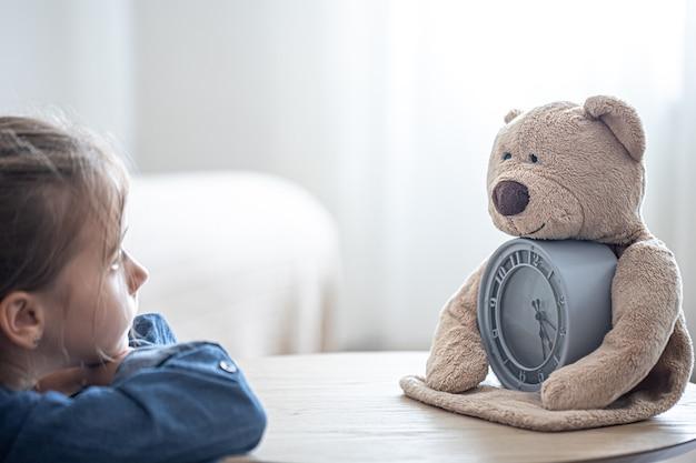 小さな女の子は悲しいことに、ぼやけた背景に目覚まし時計でテディベアを見ています。