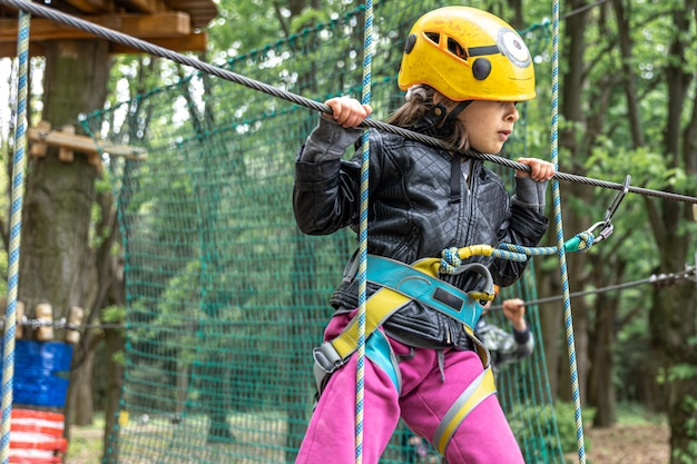 A little girl in a safety helmet climbs the ropes in the forest adventure park.